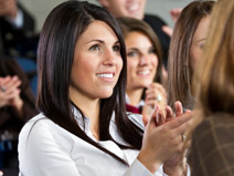 Young woman clapping at a seminar